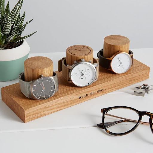 Watch display holder rests on a table, made of a long, wooden block base with 3 thick round columns sticking up enough for a watch band to sit sideways. Customizable text etched into the block base. Watch dial etched into top of the middle column.